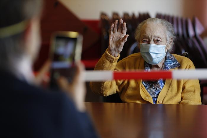 Margarite Mouille, de 94 años, gesticula mientras su hija le toma una foto en una residencia para ancianos de Kaysersberg, Francia, el 21 de abril del 2020. Francia volvió a permitir esas visitas, aunque muy reguladas, siempre con una mesa y una cinta roja y blanca de por medio.
