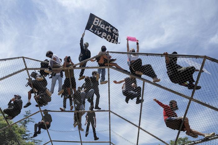 Gente sobre una estructura de bateo durante una protesta por la muerte de George Floyd en Los Ángeles, el sábado 30 de mayo de 2020.
