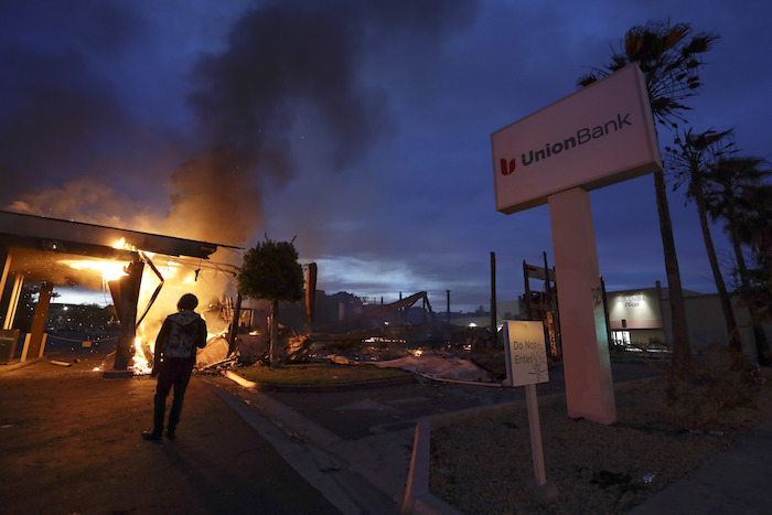 Una persona en la Mesa, California, observa mientras se incendia un banco durante los disturbios por la muerte hace unos días de George Floyd en Minneapolis, el domingo 31 de mayo de 2020.