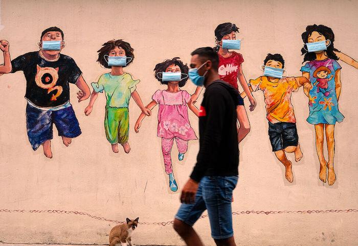 Un hombre con mascarilla camina junto a un mural en Ipoh, Malasia.