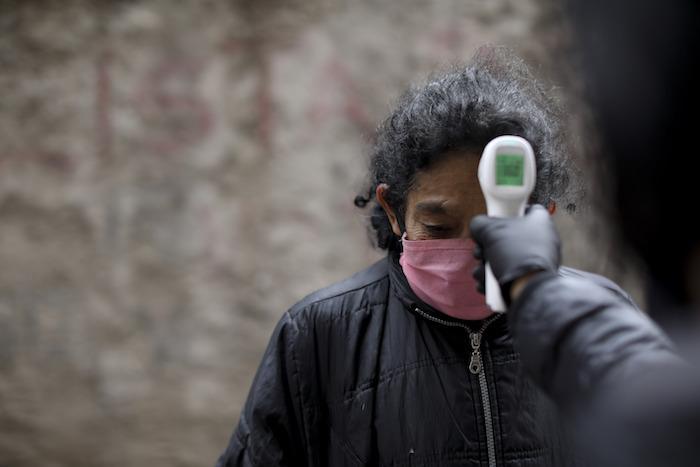Un voluntario mide la temperatura de residentes dentro del barrio marginal de Fraga durante un confinamiento ordenado por el Gobierno para frenar la propagación del nuevo coronavirus, en Buenos Aires, Argentina, el sábado 6 de junio de 2020.