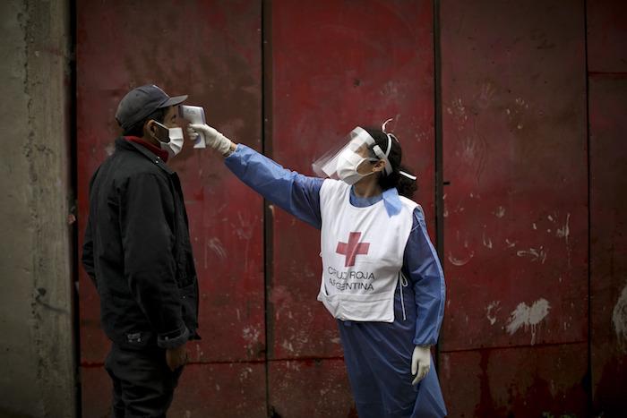 Una voluntaria de la Cruz Roja mide la temperatura de un residente dentro del barrio marginal de Fraga durante un confinamiento ordenado por el Gobierno para frenar la propagación del nuevo coronavirus, en Buenos Aires, Argentina, el sábado 6 de junio de 2020.