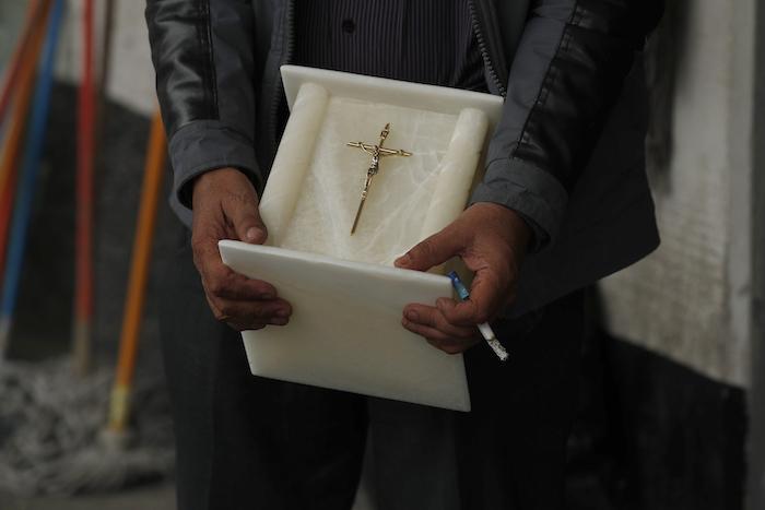 Con un cigarrillo en la mano, un hombre sostiene una urna para cenizas humanas mientras observa el cuerpo de un familiar, que murió de COVID-19, mientras trabajadores lo llevan al interior del crematorio en el Panteón San Nicolás Tolentino en la Alcaldía Iztapalapa, Ciudad de México, el martes 2 de junio de 2020.