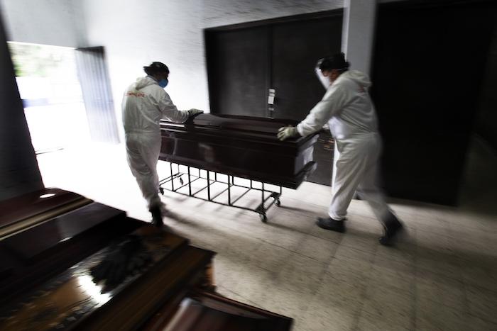 Trabajadores con equipo protector durante la pandemia del nuevo coronavirus retiran un ataúd después de colocar un cuerpo en el horno en el crematorio del Panteón San Nicolás Tolentino en la Alcaldía Iztapalapa, Ciudad de México, el jueves 4 de junio de 2020.
