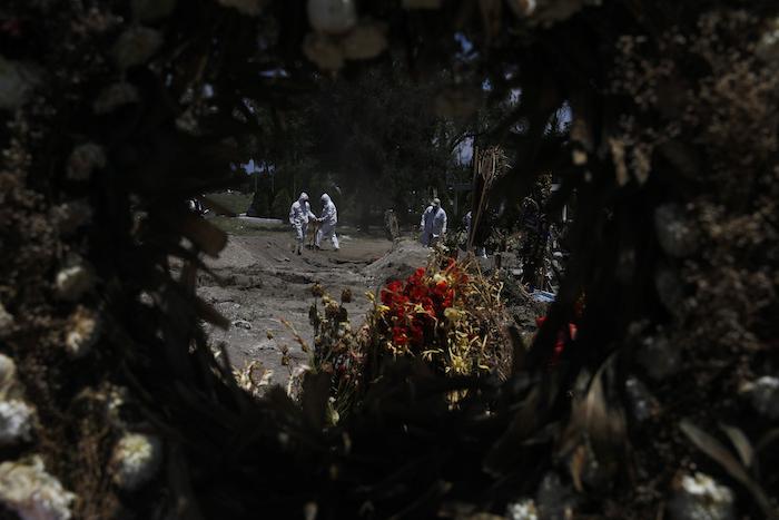 Empleados de cementerio en equipo protector entierran a víctimas de COVID-19 en el Panteón de San Lorenzo Tezonco en una sección reservada para personas que murieron del nuevo coronavirus en la Alcaldía Iztapalapa en Ciudad de México, el lunes 2 de junio de 2020. Los empleados cargan los ataúdes solos, un trabajo que en el pasado pudieron haber realizado los dolientes.