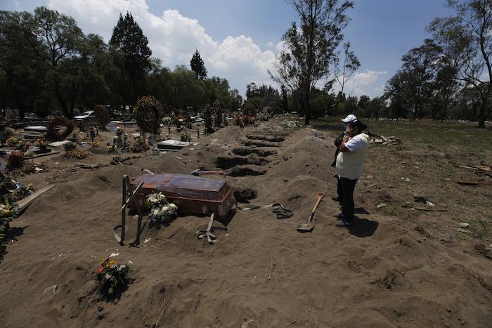 Personas ven el ataúd de un familiar que murió de COVID-19 antes de descender a una tumba en el Panteón de San Lorenzo Tezonco Iztapalapa en una sección reservada para víctimas del nuevo coronavirus en la Alcaldía Iztapalapa en Ciudad de México, el martes 2 de junio de 2020. Bajo una norma especial para contener la propagación de la pandemia, sólo se permite que dos familiares acompañen al ataúd a la tumba.