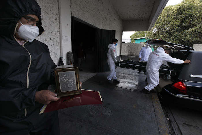 Un hombre que sostiene una urna observa el cadáver de un familiar que murió de COVID-19 mientras empleados lo llevan al crematorio del Panteón San Nicolás Tolentino en la Alcaldía Iztapalapa en Ciudad de México el martes 2 de junio de 2020.