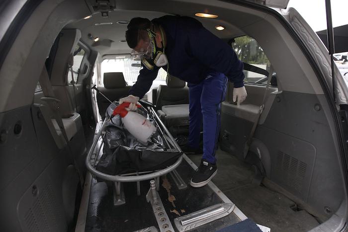 Un empleado de una funeraria rocía una bolsa que contiene un cadáver antes de ser llevada al crematorio del Panteón San Nicolás Tolentino en la Alcaldía Iztapalapa en Ciudad de México el martes 2 de junio de 2020.