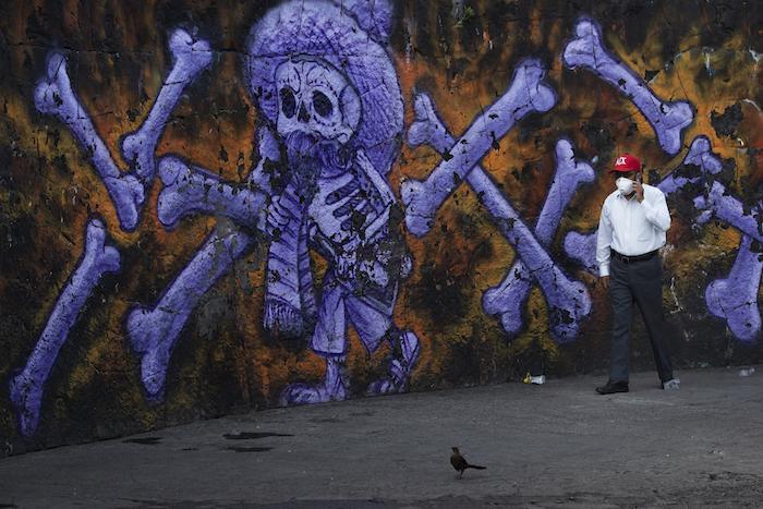 Arturo Morales Torres, responsable de varios cementerios públicos, habla en su celular frente a un mural de un esqueleto y huesos que decora el exterior del Panteón San Nicolás Tolentino en la Alcaldía Iztapalapa en Ciudad de México el jueves 4 de junio de 2020 durante la pandemia del nuevo coronavirus.