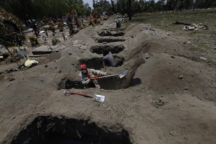 """Melvin Sanaurio, frente, cava una tumba en el cementerio San Lorenzo Tezonco en Ciudad de México el martes 2 de junio de 2020 durante la pandemia del nuevo coronavirus. """"En cada una de ellas nos demoramos más de una hora"""", dijo Sanuario."""