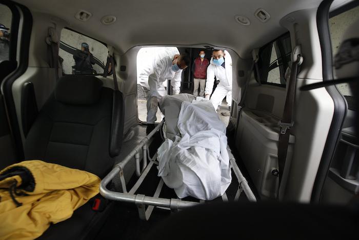 Jorge Eduardo Morales, izquierda, retira el cuerpo de una víctima de COVID-19 para llevarlo al crematorio del Panteón San Nicolás Tolentino en donde trabaja desde que tiene 18 años, en la Alcaldía Iztapalapa en Ciudad de México el martes 2 de junio de 2020.