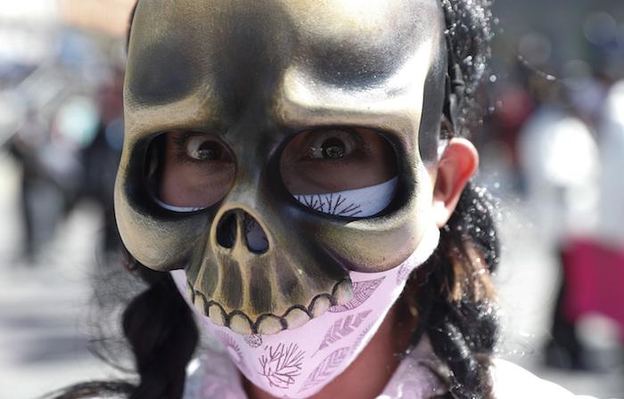 Un artista usando una mascarilla contra la pandemia del coronavirus bajo una máscara de calavera marcha para protestar contra el Gobierno en La Paz, Bolivia, el lunes 8 de junio de 2020.