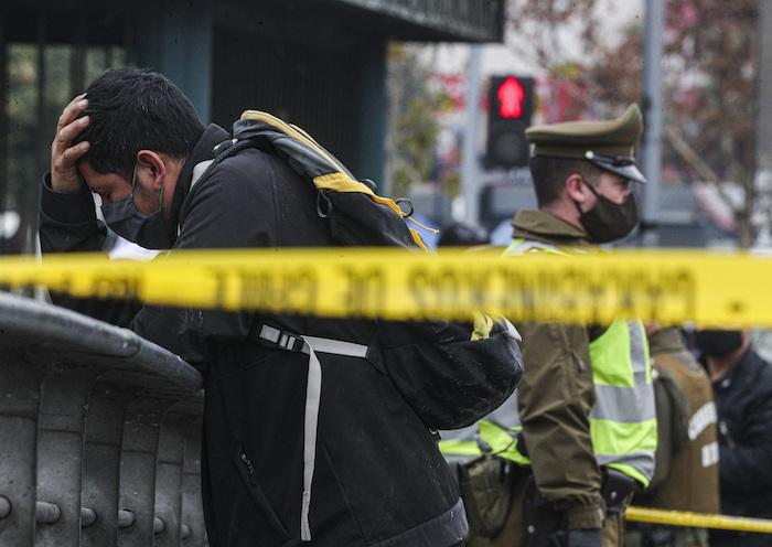 Un migrante peruano es detenido por aparecer en una base de datos policiales como positivo para COVID-19, en el centro de Santiago, Chile, el lunes 8 de junio de 2020. La policía ha rodeado el área alrededor del hombre con cinta policial para evitar que las personas entren en contacto con él.