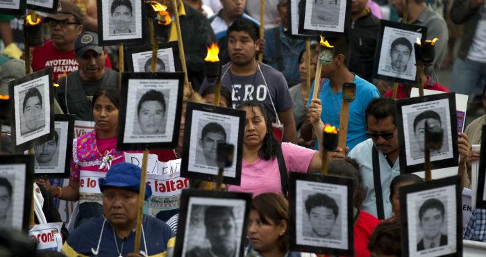En esta foto del 26 de abril de 2016, familiares y activistas de 43 estudiantes normalistas desaparecidos en el estado de Guerrero portan sus retratos para exigir que no se cierre el caso en Ciudad de México.