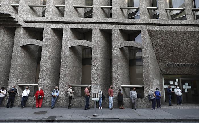 Clientes de un banco guardan su distancia para protegerse del coronavirus mientras hacen fila el lunes 29 de junio de 2020, en la Ciudad de México.