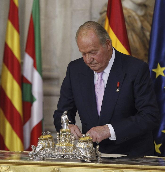 El rey Juan Carlos durante la firma de la ley orgánica que hizo efectiva su abdicación, en una solemne ceremonia celebrada en el Salón de Columnas del Palacio Real. Foto: Fernando Alvarado, Archivo EFE
