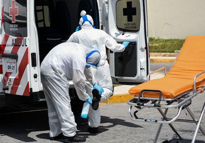 Paramédicos de la Cruz Roja desinfectan sus trajes y la ambulancia después de trasladar a un paciente con COVID-19 al hospital general de Cancún.