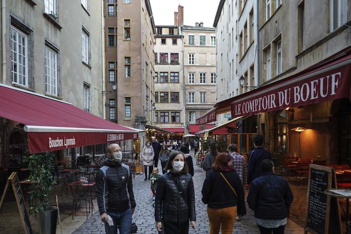 Personas con mascarilla para protegerse del coronavirus pasan frente a restaurantes el sábado 10 de octubre de 2020 en el centro de Lyon, Francia.