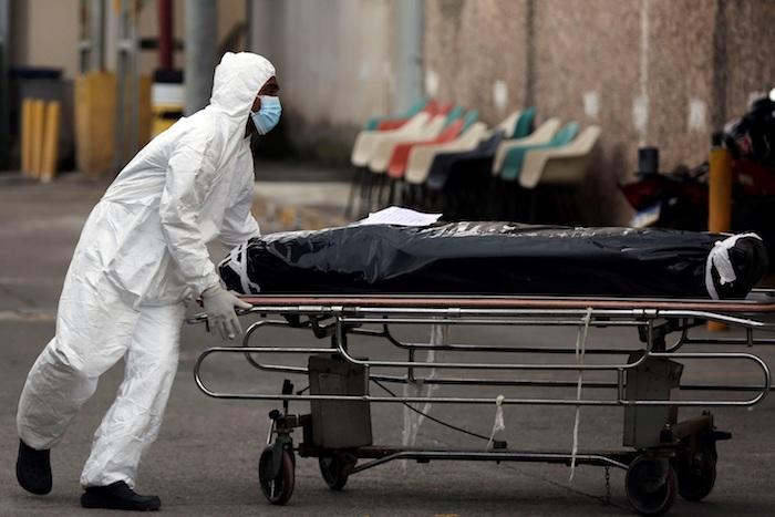 Un enfermero vestido con traje de bioseguridad traslada el cuerpo de una persona que murió en el Hospital Escuela Universitario, el 27 de octubre del 2020, en Tegucigalpa (Honduras).