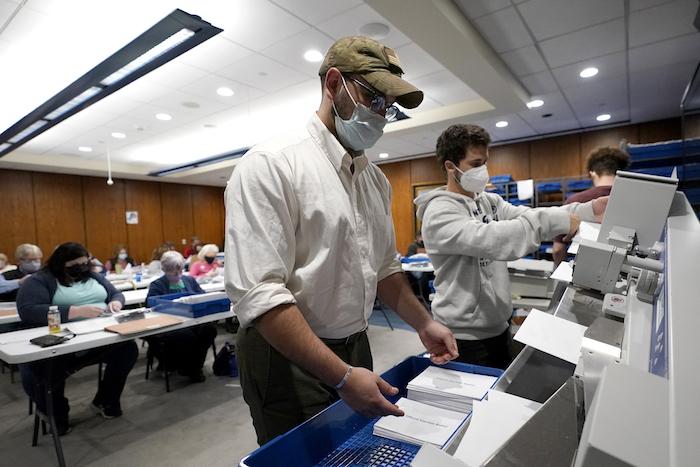 Trabajadores electorales colocan los sobres de votos por correo en una máquina antes de que sean contabilizados en Harrisburg, Pensilvania.