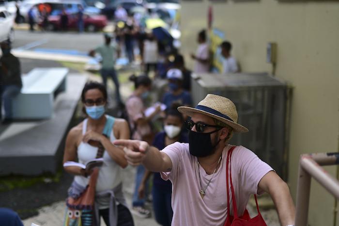 Votantes, con mascarilla por la pandemia del coronavirus, esperan en fila para depositar sus boletas en las elecciones generales, en un centro de votación habilitado en la escuela Rafael Labra, en San Juan, Puerto Rico, el 3 de noviembre de 2020.