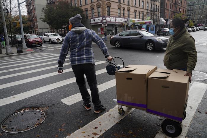 Yahaira Saavedra, a la derecha, copropietaria del restaurante mexicano La Morada, y el voluntario Dan Zimberg, a la izquierda, cruzan una calle empujando un carrito lleno de comidas en caja preparadas en el restaurante el miércoles 28 de octubre de 2020, en Nueva York.