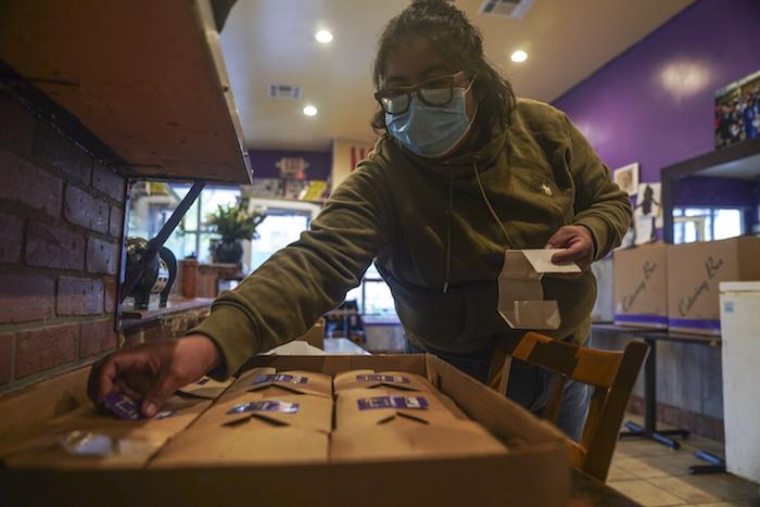 """Yajaira Saavedra coloca calcomanías que dicen """"La Morada Bx Mutual Aid Kitchen"""" en cajas de comida en su restaurante que se están preparando para distribuir en su vecindario del sur del Bronx, el miércoles 28 de octubre de 2020, en Nueva York."""