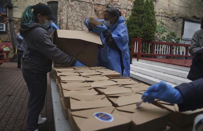 Voluntarios descargan comidas en caja preparadas en el restaurante La Morada del sur del Bronx, el miércoles 28 de octubre de 2020, en Nueva York.