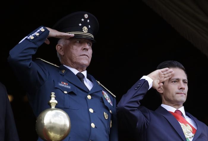 En esta imagen del 16 de septiembre de 2016, el entonces Secretario de Defensa, General Salvador Cienfuegos, a la izquierda, acompaña al Presidente de México Enrique Peña Nieto, durante el desfile militar por el Día de la Independencia en la plaza principal de la Ciudad de México.