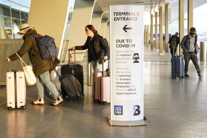 Un aviso sobre los protocolos para la prevención de COVID-19 junto a la zona de ingreso de pasajeros en la Terminal C del aeropuerto La Guardia de Nueva York, el miércoles 25 de noviembre de 2020. Foto: AP Foto, John Minchillo.