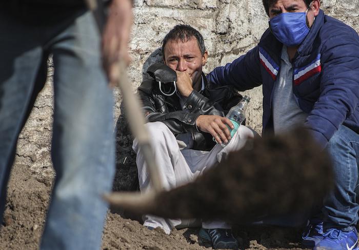El migrante peruano José Collantes llora mientras observa a los trabajadores del cementerio enterrar a su esposa Silvia Cano, quien según dijo murió de complicaciones de COVID-19, en el Cementerio Católico en Santiago, Chile, el viernes 3 de julio de 2020.