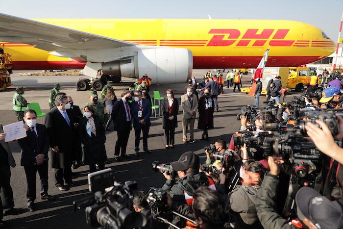 La prensa fotografía a funcionarios mientras se retira el primer envío de la vacuna Pfizer COVID-19 a México, arriba a la derecha, luego de ser descargado de un avión de carga de DHL en el Aeropuerto Internacional Benito Juárez en la Ciudad de México, el miércoles 23 de diciembre de 2020.