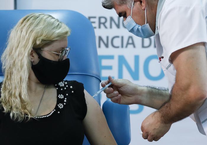 """El enfermero Gustavo Rodríguez le da a la enfermera Florencia Arroyo una inyección de la vacuna rusa """"Sputnik V"""" contra la COVID-19 en el Hospital Dr. Pedro Fiorito en Avellaneda, Argentina, el martes 29 de diciembre de 2020."""