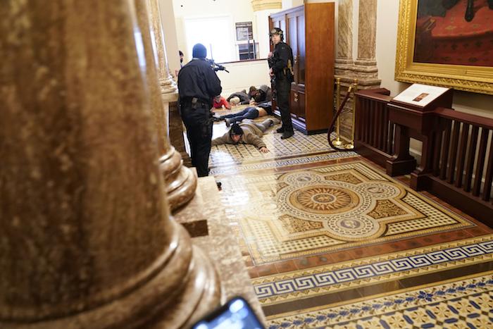 Agentes de la policía del Capitolio retienen a punta de pistola a unos manifestantes cerca del recinto de la Cámara de Representantes, en el Capitolio, en Washington, el miércoles 6 de enero de 2021.