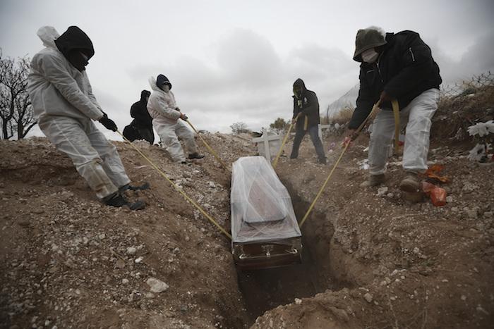 Fotografía de archivo del 27 de octubre de 2020 de trabajadores con equipo total de protección por la pandemia de coronavirus depositando un ataúd en una zona del cementerio municipal San Rafael, en Ciudad Juarez, México, que fue asignada para personas que murieron de COVID-19.
