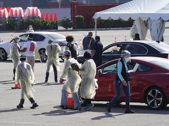 Personas aguardan dentro de sus vehículos en fila en un sitio de vacunación contra la COVID-19 fuera de The Forum en Inglewood, California, el martes 19 de enero de 2021.