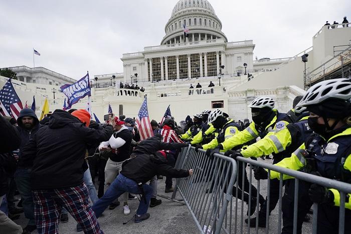En esta foto de archivo del 6 de enero de 2021, partidarios del entonces Presidente Donald Trump tratan de atravesar una barrera policial en el Capitolio en Washington.