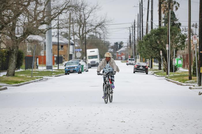 Un hombre monta una bicicleta el lunes 15 de febrero de 2021 cerca de Rosewood, Houston.