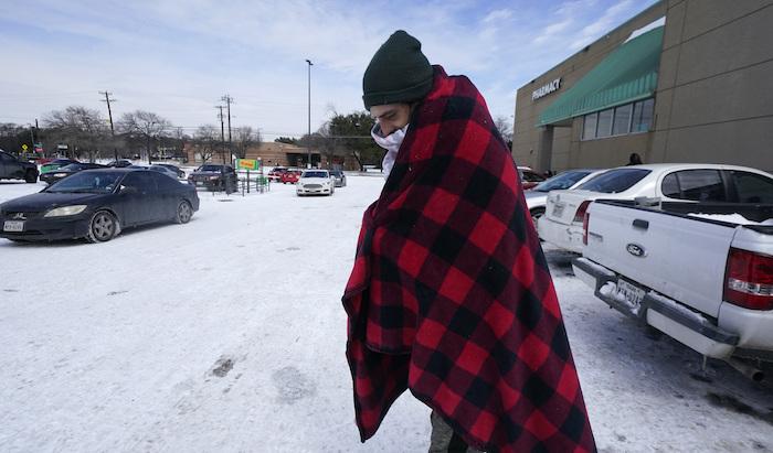 Cody Jennings utiliza un cobertor para mantenerse caliente afuera de una tienda en Dallas, el martes 16 de febrero de 2021.