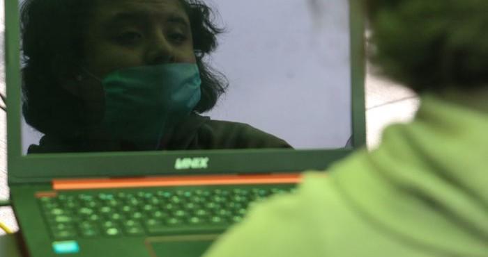 Una mujer frente a una laptop.