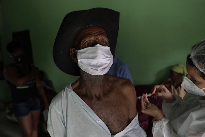 Con mascarilla para protegerse del coronavirus, Algemiro Dias, de 82 años, recibe la primera inyección de la vacuna de Sinovac contra la COVID-19, en la comunidad Kalunga Vao de Almas, una zona rural a las afueras de Cavalcante, en el estado de Goias, Brasil, el 15 de marzo de 2021.