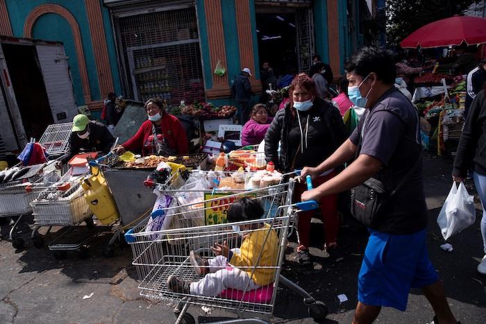 Un grupo de personas es visto hoy, en los alrededores de la Vega Central de Santiago (Chile).