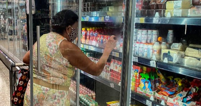 Una mujer compra alimentos en el refri del supermercado.