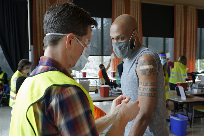 Shawn Brown, derecha, recibe una segunda dosis de la vacuna de Moderna contra el coronavirus de parte de un voluntario en un centro masivo de vacunaciones en Seattle, Washington, el viernes, 26 de febrero del 2021.