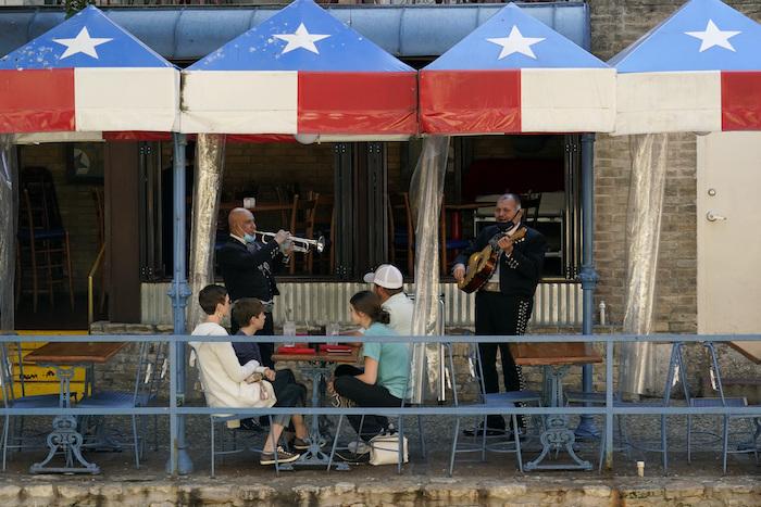 En esta fotografía de archivo del 3 de marzo de 2021, dos mariachis tocan para comensales en un restaurante junto al río en San Antonio, Texas.