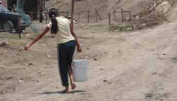 Mujer acarrea cubeta de agua en Guerrero