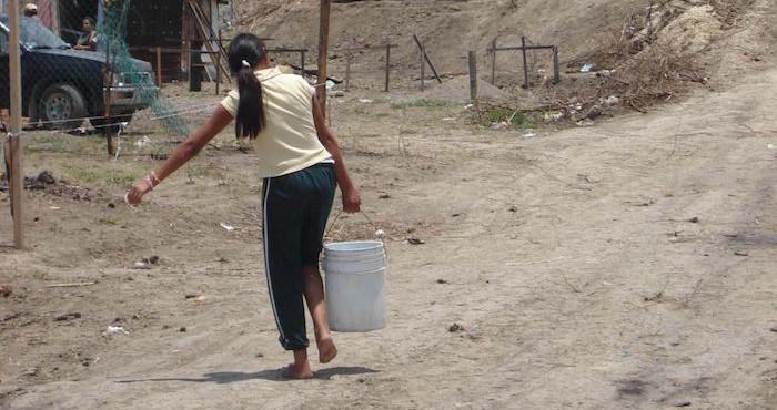 Una mujer acarrea una cubeta de agua en Guerrero.