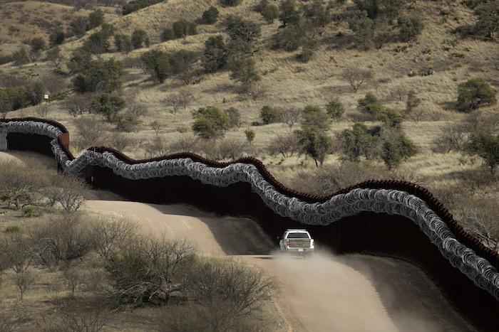 En esta imagen del 2 de marzo de 2019, un agente de la Oficina de Aduanas y Protección Fronteriza de Estados Unidos patrulla el lado estadounidense de un muro con alambre de cuchillas junto a al frontera con México, al este de Nogales, Arizona.