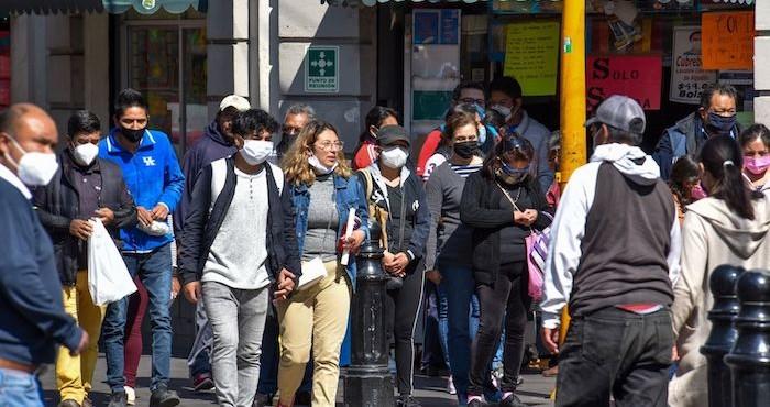 Personas con cubrebocas caminan por las calles del Centro Histórico de la Ciudad de México.