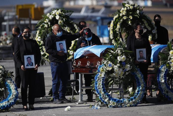Personas de pie esperan con fotografías mientras las familias reciben los restos de 16 migrantes guatemaltecos que fueron asesinados cerca de la frontera entre Estados Unidos y México en enero que llegaron a la base de la Fuerza Aérea en Ciudad de Guatemala, el viernes 12 de marzo de 2021.